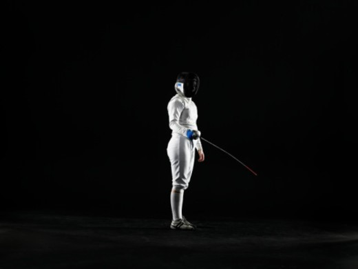 Female (14-16) fencer holding foil, side view : Stock Photo