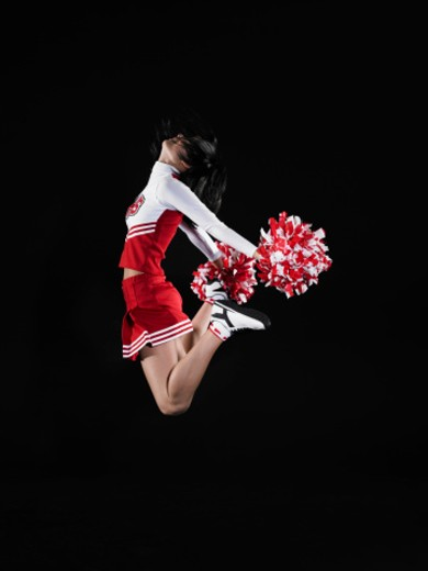 Stock Photo: 1527R-1203017 Young female cheerleader jumping in midair, head back, side view