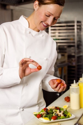 Female chef placing cherry tomatoes atop salad in commercial kitchen : Stock Photo