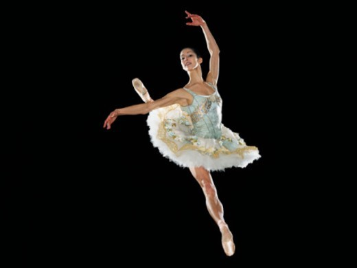 Young female ballerina jumping in midair, portrait : Stock Photo