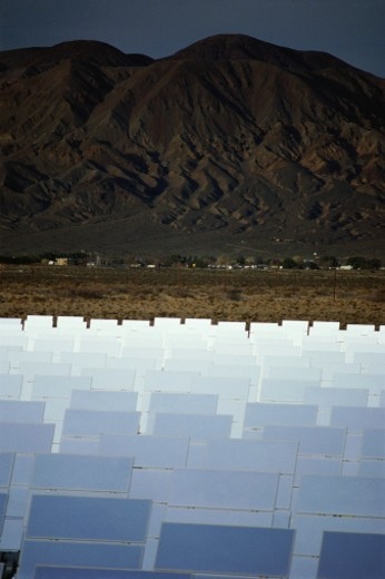 Stock Photo: 1527R-1205634 Solar plant against hill and dark sky