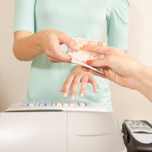 Teenage girl paying at till, close-up : Stock Photo