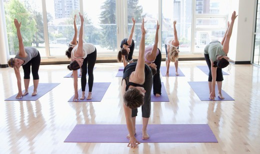 Stock Photo: 1527R-1207234 class practicing yoga with instructor in a bright room surrounded with glass