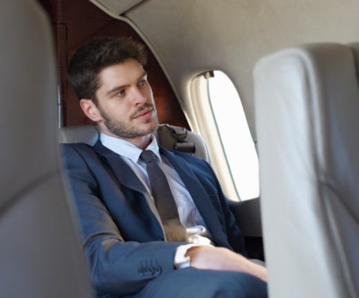 Stock Photo: 1527R-1207735 Young business man relaxing on a plane