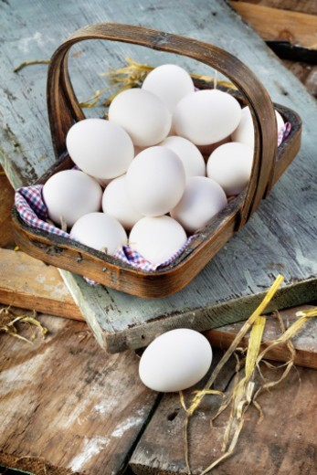 A garden trug filled with white duck eggs on wooden surfaces with straw : Stock Photo