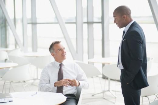 Businessmen talking in lobby : Stock Photo
