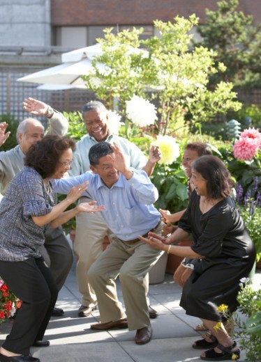 Senior friends dancing at outdoor party : Stock Photo