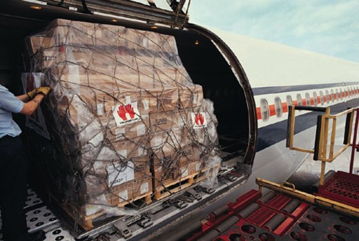 Cargo being loaded onto airplane : Stock Photo