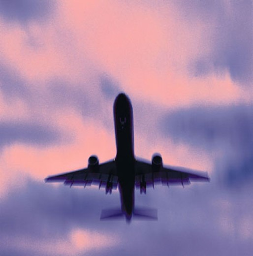 Stock Photo: 1527R-158019 Silhouetted plane in pink and purple sky
