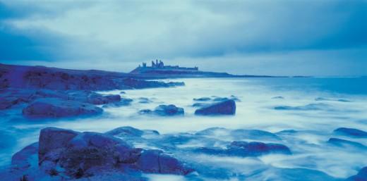 Gloomy coastline with distant castle : Stock Photo