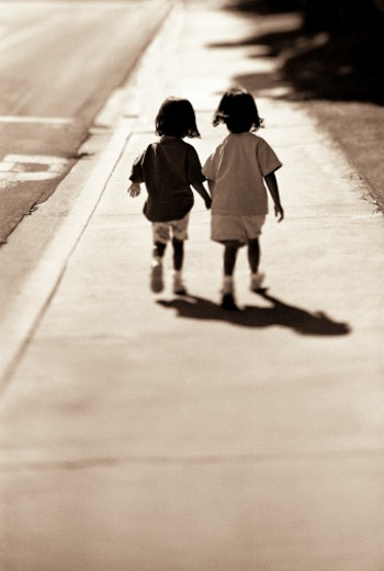 Two sisters walking down sidewalk : Stock Photo