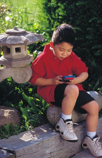 Young boy sitting and playing hand held video game : Stock Photo