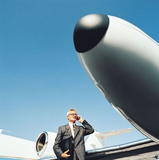 Stock Photo: 1527R-308089 Businessman Using a Mobile Phone by an Airplane