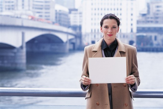 Woman holding a blank piece of paper : Stock Photo
