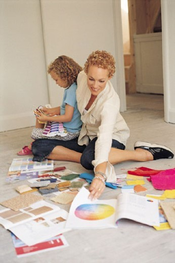 Stock Photo: 1527R-384071 Woman Looking at Color Samples, Child on Her Lap