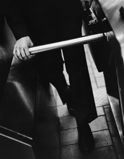 Stock Photo: 1527R-398007 Businessman Going Through Turnstile