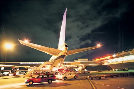 Vehicles Around Airplane at Night : Stock Photo