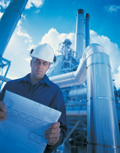 Stock Photo: 1527R-415022 Man reading blueprint in front of power station