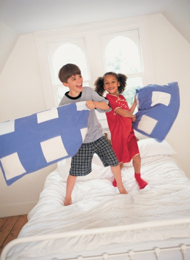 Two Children Having a Pillow Fight : Stock Photo
