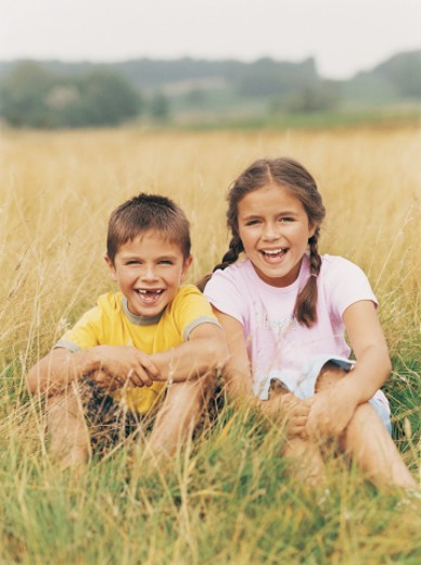 Stock Photo: 1527R-449027 Portrait of a Brother and Sister Sitting in a Field