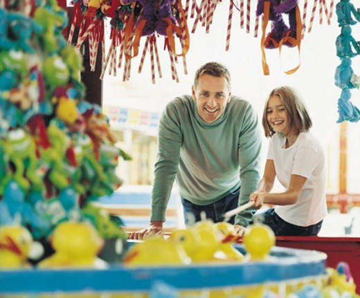 Stock Photo: 1527R-449034 Father and Daughter at a Fishing Game at An Amusement Park