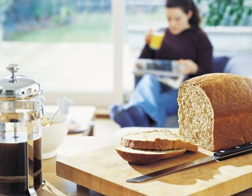 Stock Photo: 1527R-472029 Loaf of Bread with a Woman Reading a Newspaper in the Background