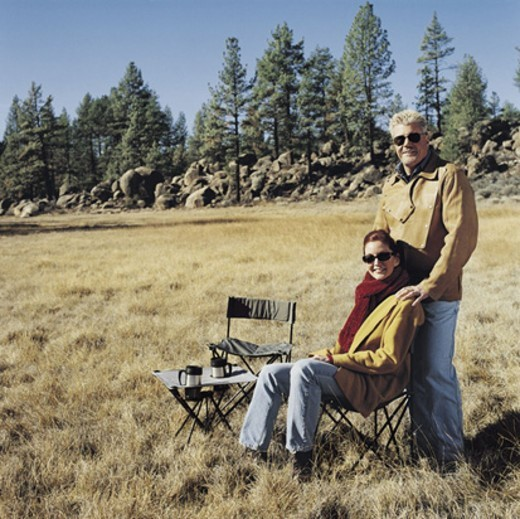 Portrait of a Man Standing With a Woman in a Field by a Camping Chair and Table : Stock Photo