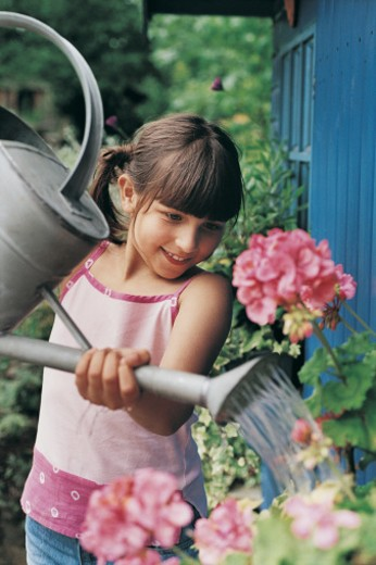 Stock Photo: 1527R-493019 Girl Watering Flowers Near Garden Shed