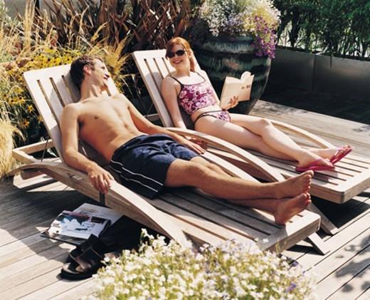 Stock Photo: 1527R-493039 Couple Sunbathing in Their Garden