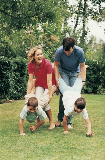 Family Having a Wheelbarrow Race in Their Garden : Stock Photo