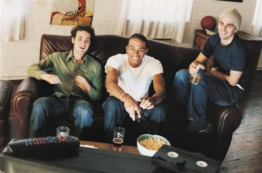 Three Men on the Sofa Watching TV : Stock Photo