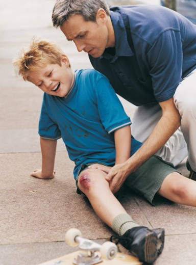 Stock Photo: 1527R-502086 Man Helping Boy After a Skateboard Accident
