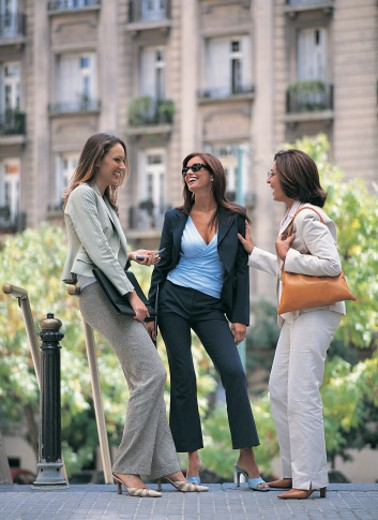 Stylish Businesswomen Laughing and Chatting Outdoors on a City Pavement : Stock Photo