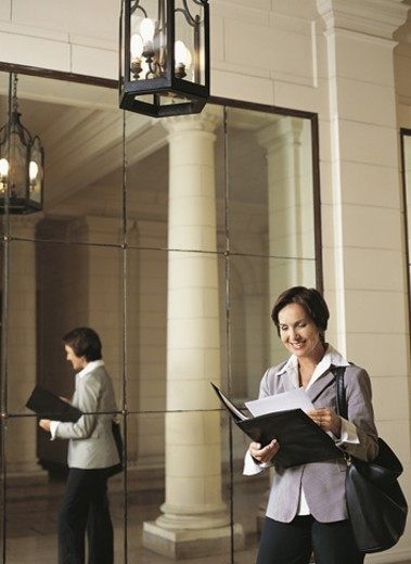 Stock Photo: 1527R-508057 Businesswoman Standing in a Covered Walkway Reading a Document