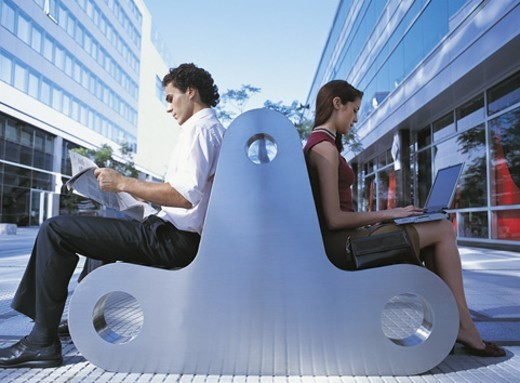 Side View of a Businesswoman and a Businessman Sitting on a Bench Back to Back Reading a Newspaper and a Using Laptop : Stock Photo