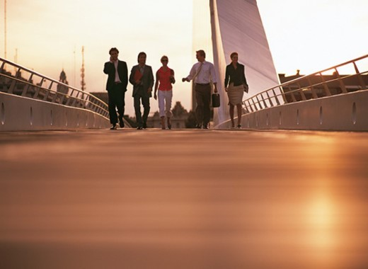 Distant View of a Group of Business People Walking Across a City Bridge : Stock Photo