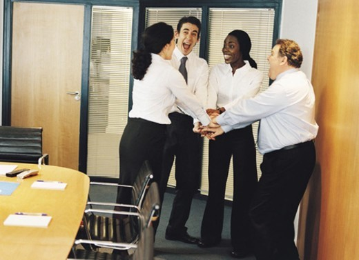 Stock Photo: 1527R-509044 Four Business Colleagues Holding Hands and Bonding in the Boardroom