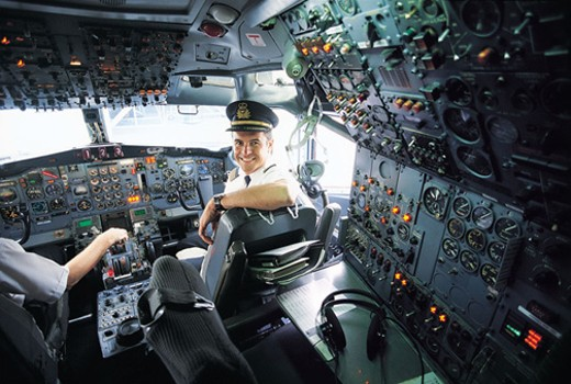 Portrait of a Pilot Sitting at the Controls of a Commercial Aeroplane : Stock Photo