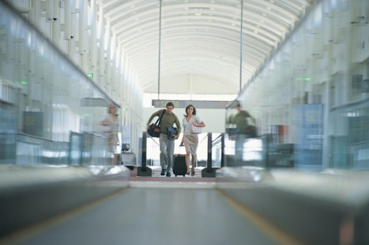 Late Couple Running Down Moving Sidewalk in an Airport : Stock Photo