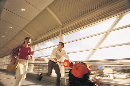 Couple Rushing Down a Corridor at the Airport, Pushing a Baggage Trolley : Stock Photo