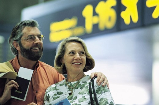 Man With His Arm Around a Woman at an Airport Holding Passport and Tickets : Stock Photo