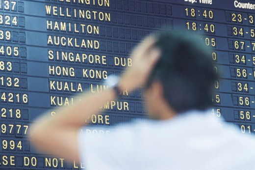 Stock Photo: 1527R-523052 Man With a Hand on His Head Looking at an Airport's Arrival Departure Board