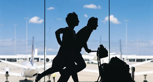 Couple Pushing a Baggage Trolley Late for Their Plane : Stock Photo