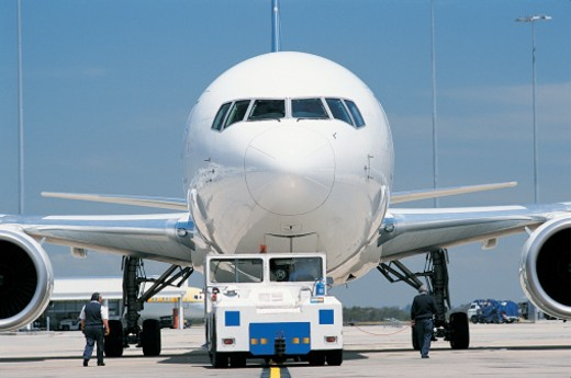 Stock Photo: 1527R-523080 Commercial Aeroplane Being Towed by an Airport Vehicle
