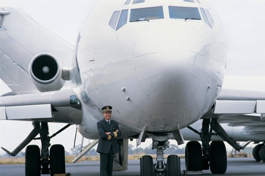 Portrait of a Pilot Standing Next to an Aeroplane : Stock Photo