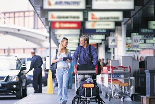 Couple Pushing a Baggage Trolley Outside of an Airport : Stock Photo