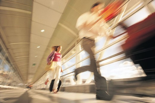 Stock Photo: 1527R-523098 Couple Rushing Down a Corridor at the Airport, Pushing a Baggage Trolley