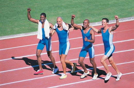 Four Athletes Celebrating Success on the Running Track : Stock Photo