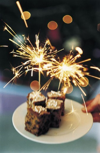 Stock Photo: 1527R-526047 Hand Holding a Christmas Cake and Sparklers