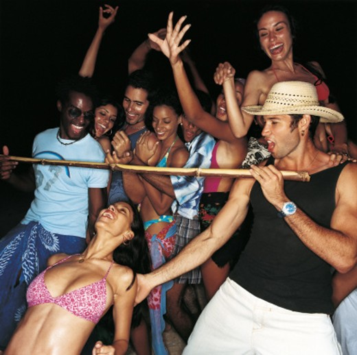 Woman Doing the Limbo at a Crowded Party : Stock Photo